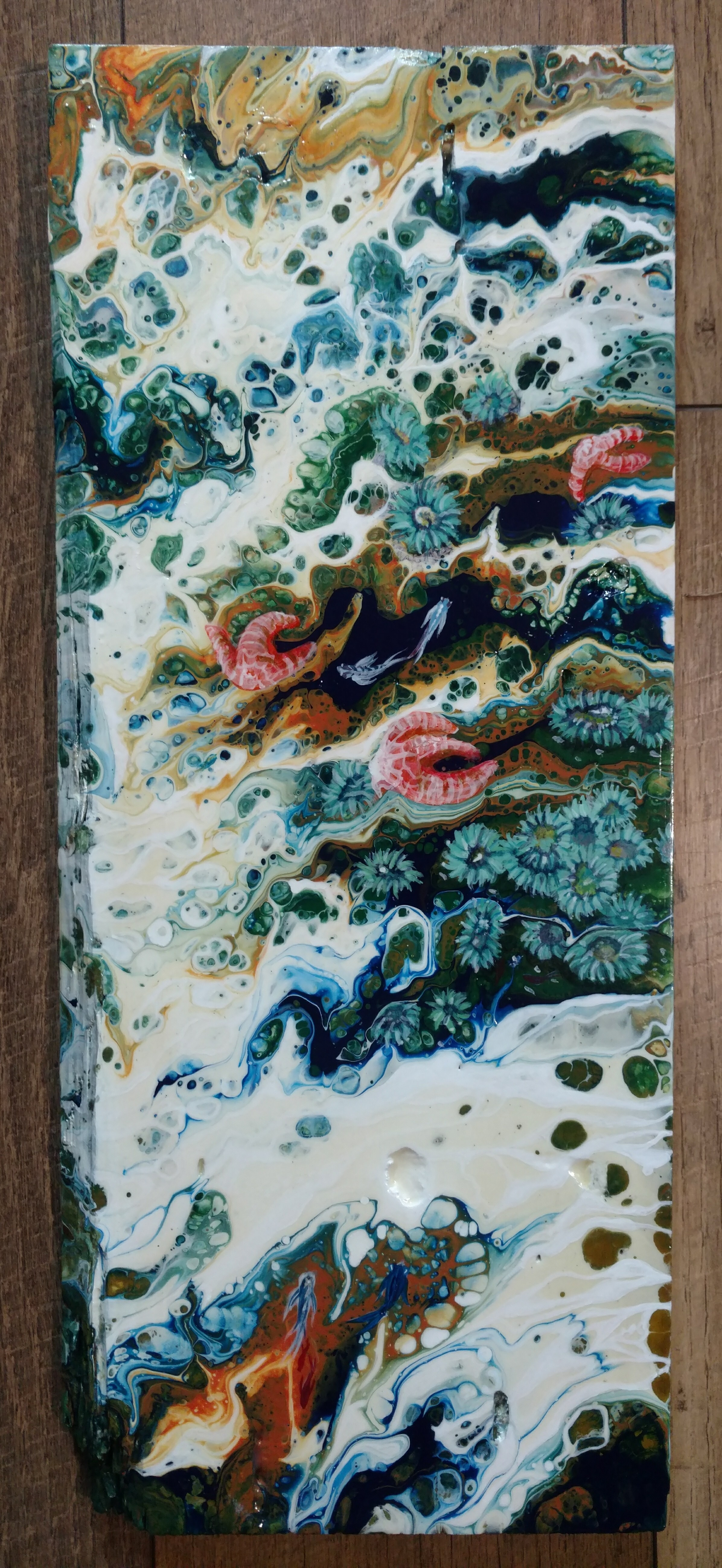This piece is an acrylic pour and the design is completed by adding sea creatures and foam.